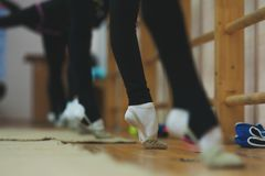 Close up of feet of girl stretching tip toe in gym. Close up of feet of young gymnast stretching tip toes at the gym club. Close up of feet of toe-pointing of royalty free stock photos