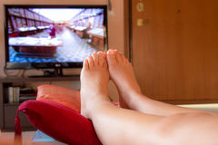 Close-up on the feet of a girl watching TV Royalty Free Stock Photography