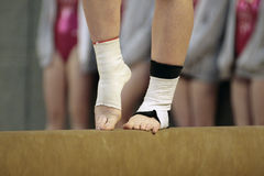 Close up of feet of a gymnast on a beam. A gymnast prepares for movement on a beam at a women's competition. The picture offers a close-up on the feet and ankles Stock Images