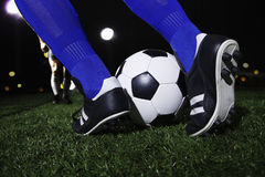 Close up of feet kicking the soccer ball, night time in the stadium stock photography