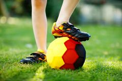 Close-up of feet of kid boy with football and soccer shoes in German national colors - black, gold and red. World or. Europe cup concept royalty free stock photos