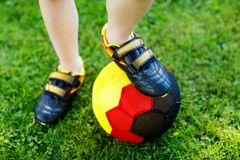 Close-up of feet of kid boy with football and soccer shoes in German national colors - black, gold and red. World or. Europe cup concept royalty free stock photography