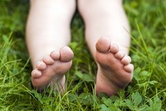 Close up of feet of little girl on green grass.  Royalty Free Stock Image