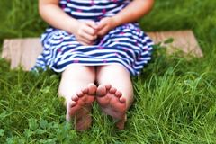 Close up of feet of little girl on green grass.  Royalty Free Stock Photos