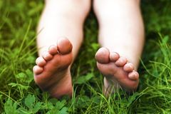 Close up of feet of little girl on green grass royalty free stock photos