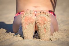 Girls feet on the beach. Close up of a feet of a little girl sitting on the beach in summer royalty free stock photos