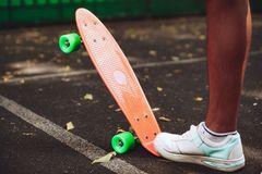 Close up of feet of man sneakers rides on orange penny. Skateboard on asphalt Stock Image