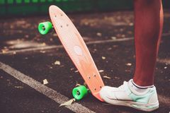 Close up of feet of man sneakers rides on orange penny. Skateboard on asphalt Royalty Free Stock Photography