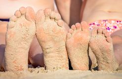 Girls feet on the beach. Close up of a feet of a mother and her little daughter girl sitting together on the beach in summer Stock Photo