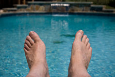 Close up of feet over pool. Middle aged male feet overhanging a blue swimming pool stock photos