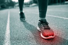 Close up of feet with red spot running on track. Fitness, sport, sports injury, pain and people concept - monochrome close up of woman feet or legs running on stock image
