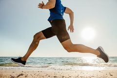 Close-up feet runner man. Running on beach in sunlight royalty free stock photography
