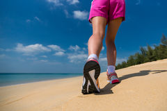 Close up of feet of a runner running in the beach training for marathon Stock Photography