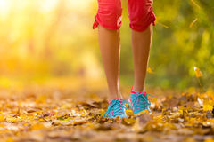 Close up of feet of a runner running in leaves. Close up of feet of woman runner running in autumn leaves, concept of training exercise stock images