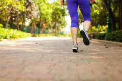 Close up of feet of runner running in park training for marathon and fitness healthy lifestyle. Selective focus stock photography