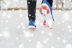 Close up of feet running along snowy winter road. Fitness, sport, people, footwear and healthy lifestyle concept - close up of male feet running along winter royalty free stock image