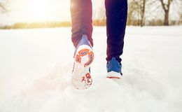 Close up of feet running along snowy winter road. Fitness, sport, people, footwear and healthy lifestyle concept - close up of male feet running along winter stock photography