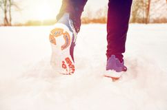 Close up of feet running along snowy winter road. Fitness, sport, people, footwear and healthy lifestyle concept - close up of male feet running along winter royalty free stock photography
