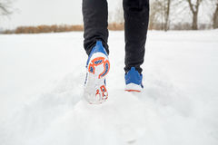 Close up of feet running along snowy winter road. Fitness, sport, people, footwear and healthy lifestyle concept - close up of male feet running along winter stock photo