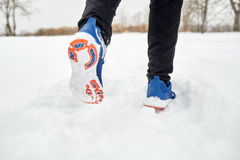 Close up of feet running along snowy winter road. Fitness, sport, people, footwear and healthy lifestyle concept - close up of male feet running along winter royalty free stock photos
