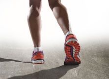 Close up feet with running shoes and female strong athletic legs of sport woman jogging Royalty Free Stock Photography