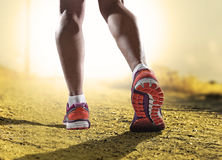 Close up feet with running shoes and female strong athletic legs of sport woman jogging in fitness training Royalty Free Stock Images