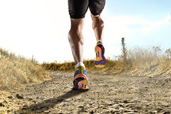 Close up feet with running shoes and strong athletic legs of sport man jogging in fitness training workout. On off road trail track design in advertising poster Royalty Free Stock Photo