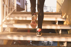 Close up of feet with sneakers climbing up the stairs Royalty Free Stock Image