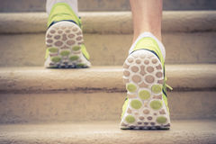 Close up of feet with sneakers climbing up the stairs Stock Photos