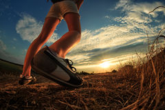 Close up of feet sportwoman in autumn grass. Close up of feet of a woman running in autumn grass against sunset royalty free stock images