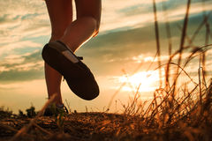 Close up of feet sportwoman in autumn grass. Close up of feet of a woman running in autumn grass against sunset royalty free stock photography