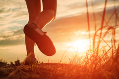 Close up of feet sportwoman in autumn grass. Close up of feet of a woman running in autumn grass against sunset stock photo