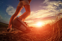 Close up of feet sportwoman in autumn grass. Close up of feet of a woman running in autumn grass against sunset stock images