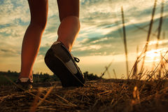 Close up of feet sportwoman in autumn grass. Close up of feet of a woman running in autumn grass against sunset royalty free stock image