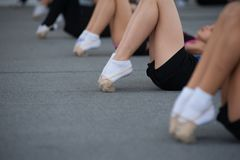 Close up of feet of girls stretching tip toes in gym royalty free stock photography