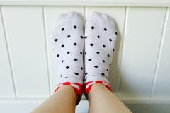 Close Up Feet Wearing White Polka Dot Socks in Bedroom Background Stock Image