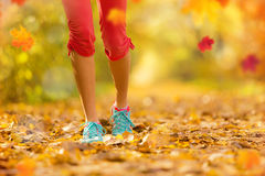 Close up of feet of woman runner in autumn. Close up of feet of woman runner running in autumn leaves, concept of training exercise stock images