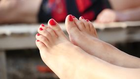 Close-up of the feet of a woman whose toes are painted with red lacquer on the sea coast. The concept of leisure and travel. Slow motion stock footage