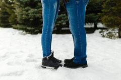 Close-up feet of a young couple in warm winter shoes standing on the snow. The legs of a man and a woman in winter boots stand on. The snow next to each other Stock Photo