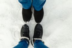 Close-up feet of a young couple in warm winter shoes standing on the snow. The legs of a man and a woman in winter boots stand on. The snow next to each other Royalty Free Stock Photo
