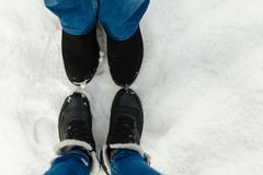 Close-up feet of a young couple in warm winter shoes standing on the snow. The legs of a man and a woman in winter boots stand on. The snow next to each other Royalty Free Stock Images