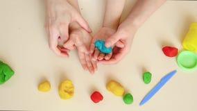 Close up feliz da mãe e da criança, mãos que jogam com figuras do plasticine, massa, modelos de mistura, vista superior video estoque