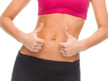 Close up of female abs and hands showing thumbs up Stock Image