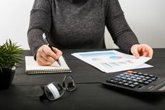Close up of female accountant or banker making calculations. Savings, finances and economy concept Stock Image