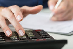 Close up of female accountant or banker making calculations. Royalty Free Stock Image