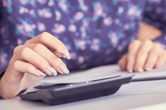 Close up of female accountant or banker hand making calculations. Savings, finances and economy concept. Close up of female accountant or banker making stock photography