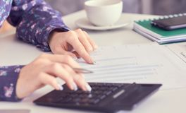 Close up of female accountant or banker hand making calculations. Savings, finances and economy concept. Close up of female accountant or banker making royalty free stock photo