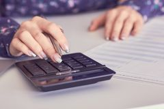 Close up of female accountant or banker hand making calculations. Savings, finances and economy concept. Close up of female accountant or banker making royalty free stock images