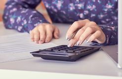 Close up of female accountant or banker hand making calculations. Savings, finances and economy concept. Close up of female accountant or banker making royalty free stock photography
