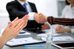 Close up of female applause while business people shaking hands at meeting Stock Images